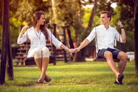 young modern stylish couple playing swings outdoor photo
