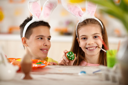 mimo: Girl with brother with long rabbit ears hold Easter egg