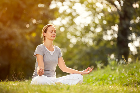 Young female relaxes in yoga pose in green nature
