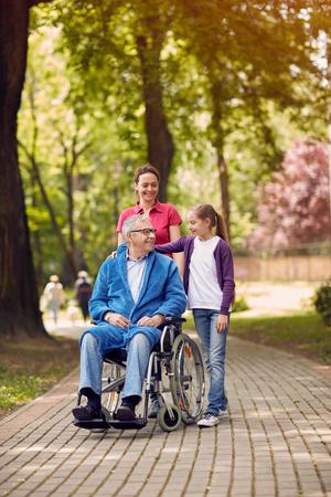 彼の娘と孫娘と共に時間を過ごす公園で男は無効 写真素材