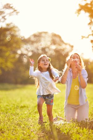 自然の中の陽気な少女チェイス シニー シャボン玉 写真素材