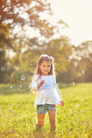 Young female child enjoy chasing soap bubbles in nature