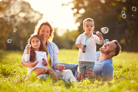 Parents with children having fun in nature with soap bubbles Stockfoto
