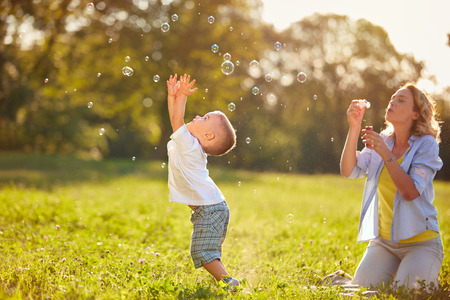 Male kid with mother having fun catching soap bubbles