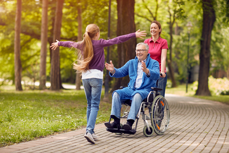 disabled grandfather in wheelchair welcoming his happy granddaughter Foto de archivo
