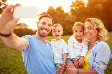 Smiling male and female with young son taking photo