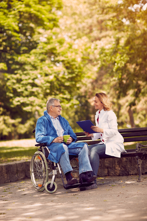 Caring nurse talking with patient in wheelchair checking up the history of the disease outdoor Stock Photo