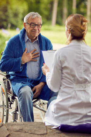 elderly man in wheelchair who dont feel good with nurse outdoor