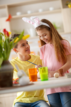 Boy and girl in kitchen painting eggs for Easter Stock Photo