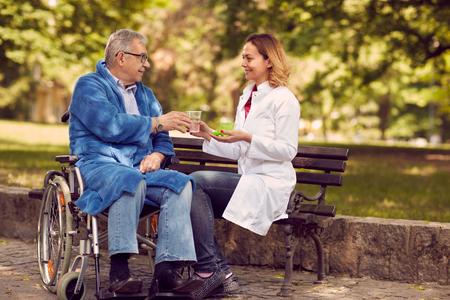 Enfermera de hospicio que da medicina de terapia al hombre mayor en silla de ruedas al aire libre