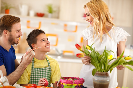 Father having fun with son while mother arranges colorful tulips in vase Stock Photo
