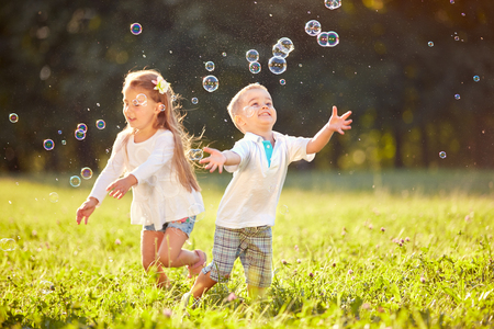 Cheerful children run and chase bubbles in nature