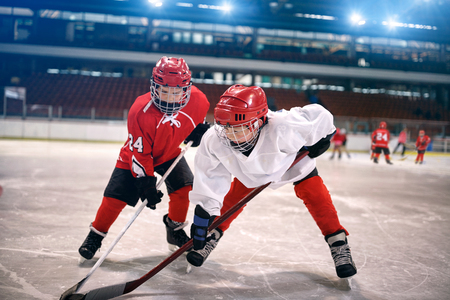 young children play ice hockey Stock Photo