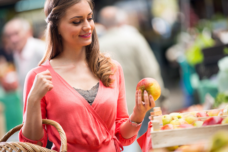 woman smiling with green apples at market store Stock Photo