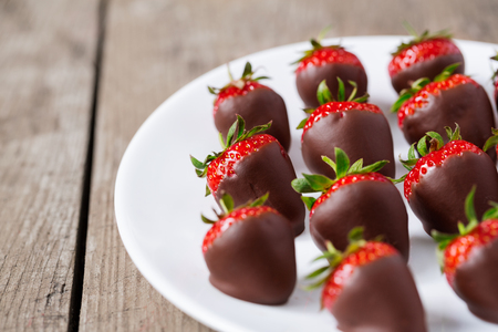 strawberries dipped in chocolate sauce on plate Stock Photo