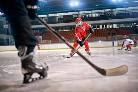 ホッケーの試合でゴールに蹴りアクションでプレーヤーのスケート リンクで