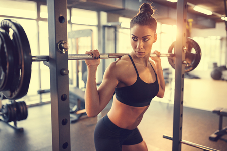 Woman with barbell doing exercise for pumping muscles in gym