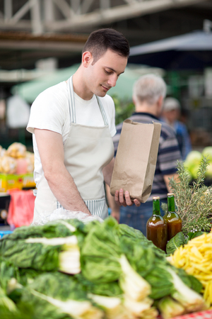 salesman standing on stall fresh food at farmer�s market