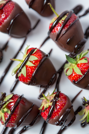 red strawberries and chocolate syrup close up Stock Photo