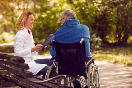 Hospice nurse checking up the history of the patient in wheelchair Stock Photo