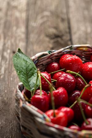 wooden basket: Fresh cherries in wicker basket on the wooden background Stock Photo