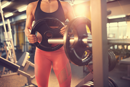Fit chica en el gimnasio de poner la rueda de metal en la máquina para el ejercicio, concepto