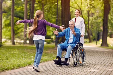 vrolijke kleinkinderen die senior gehandicapte vader in het park bezoeken
