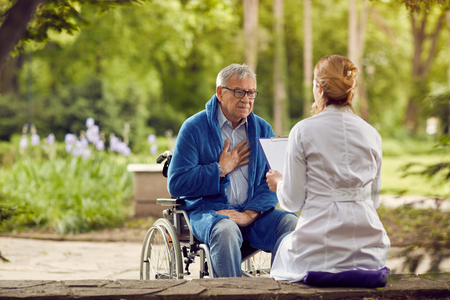 Nurse with elderly man in wheelchair who don't feel good outdoor Stockfoto