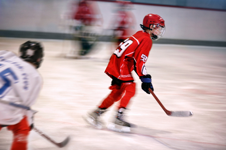 striker: young boy playing ice hockey on the rink