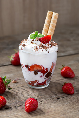 whipped cream dessert in the glass with red strawberries