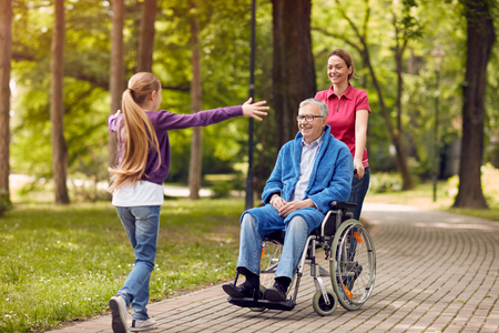 Feliz nieta la bienvenida a su abuelo con discapacidad f en silla de ruedas en el parque Foto de archivo - 76572985