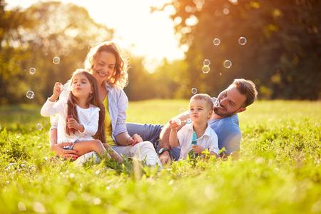 Mužské a ženské dítě vyfoukne mýdlové bubliny venku