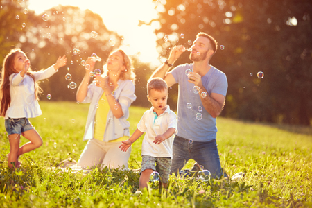 Happy children with parents enjoying in chasing soap bubbles