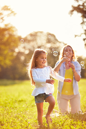 Young child play with soap bubbles in park