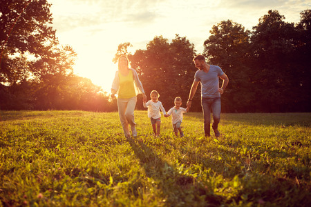 Happy young children with parents running in park Stock Photo