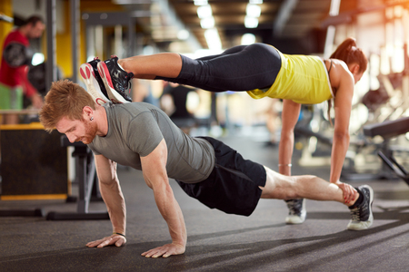 Sports couple trains together in fitness club photo