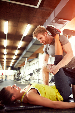 Trainer help girl in exercises in gym photo