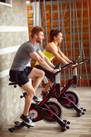 Couple trains together on exercising bike in gym
