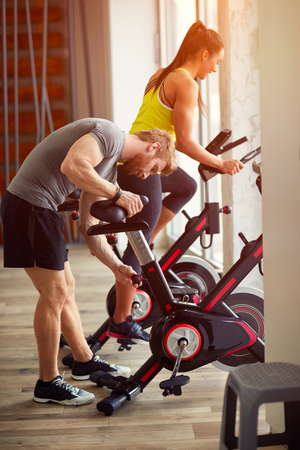 couple in gym exercise on sport bicycle on sunny day photo