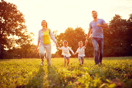 Very happy family enjoy while run on green field