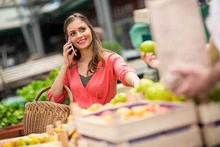 smile woman with mobile phone showing at street market