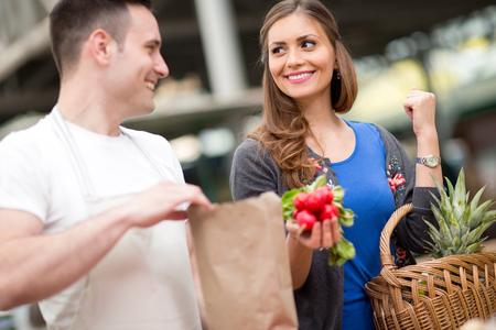 smiling woman buying radishes on the market photo