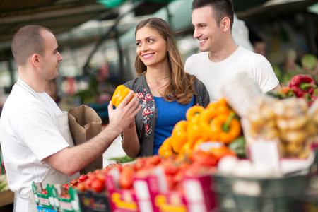 Couple buying vegetable from salesman at street market photo