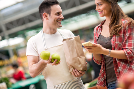 salesman and young woman looking checking list at market photo
