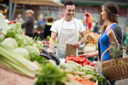 woman shopping organic vegetable at street market photo