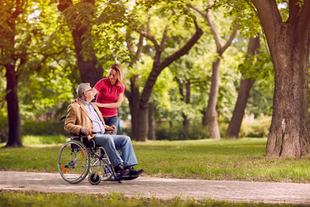 Happy senior man in wheelchair in the park with smiling daughter in the park Stockfoto