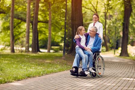 公園の若い孫娘と看護婦の車椅子を押すの年配の男性 写真素材 - 78069435