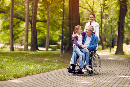 nurse pushing senior man on wheelchair with his young granddaughter in park