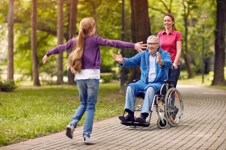 陽気な祖父の孫娘と公園で娘と一緒に楽しんでを無効に 写真素材