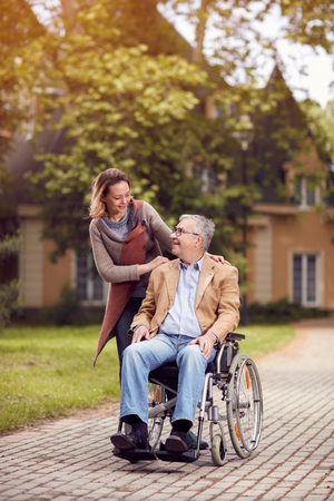 Medical: Happy caregiver daughter with senior man in wheelchair Stock Photo